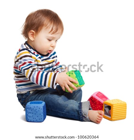 Adorable one year old child playing with toy cubes, isolated on white - stock photo
