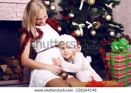 adorable photo of happy family. pregnant mother with her little cute daughter posing beside a decorated Christmas tree and presents - stock photo
