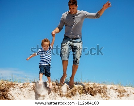 Adorable portrait of a young dad and his son jumping outdoors - stock photo