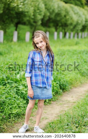 Adorable pre-teen tween kid girl with long brunette hair in blue plaid shirt and jeans skirt waking in the park  - stock photo