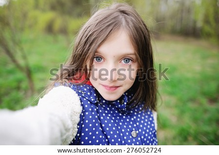Adorable pre-teen tweenie kid girl making self portrait with funny  face on her  smartphone - stock photo
