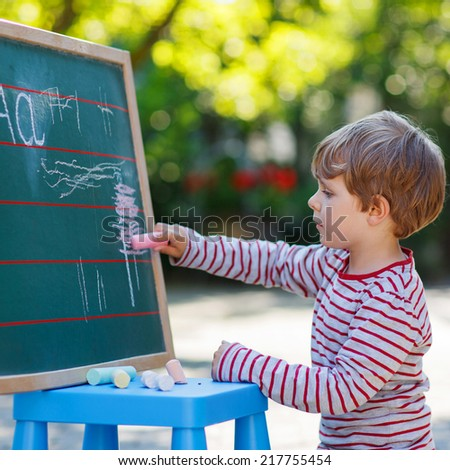 adorable preschool child at blackboard practicing writing letters, outdoor school or nursery. Square format. - stock photo
