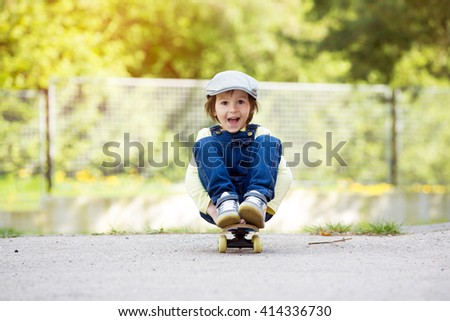 Adorable preschool child, skateboarding on the street, late spring sunny afternoon