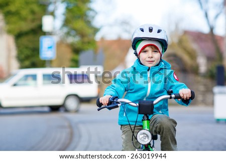 Adorable preschool kid boy riding with his first green bike in the city. Happy child in colorful clothes. Active leisure for kids outdoors. - stock photo