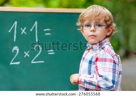 Adorable preschool kid boy with glasses at blackboard practicing mathematics, outdoor. school or nursery. Back to school concept - stock photo