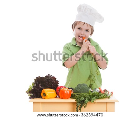 Adorable preschooler wearing a chef's hat and standing behind a small table full of vegetables taking a bite out of a carrot.  Isolated on white with room for your text.