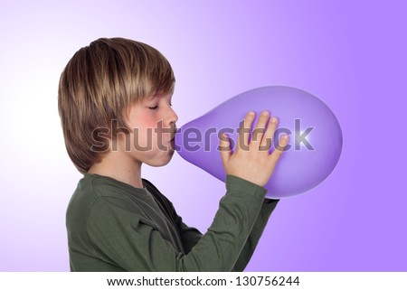 Adorable preteen boy blowing up a balloon isolated on a over purple background - stock photo