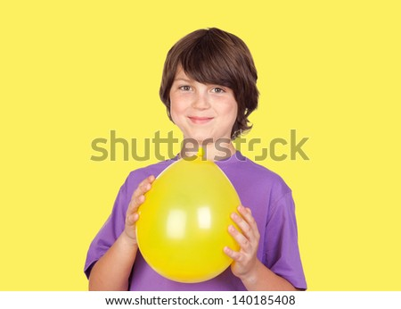 Adorable preteen boy with a balloon isolated on a over yellow background - stock photo