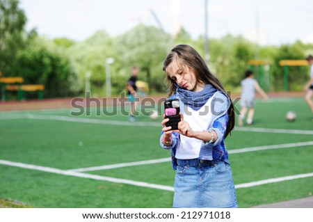 Adorable preteen kid girl making self portrait with funny duck face on her cell phone on the school soccer field  - stock photo