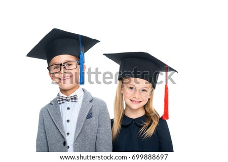 adorable pupils in graduation hats isolated on white