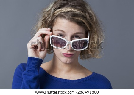 adorable 20s girl looking over her girly sunglasses - stock photo