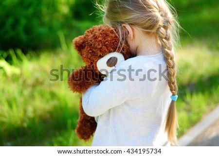 Adorable sad girl with teddy bear in park. - stock photo