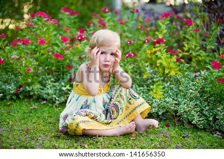 Adorable scared little girl in dress sitting in tropical blooming