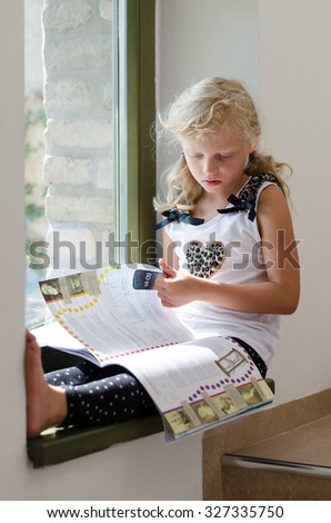 adorable scholar blond girl sitting by the window and browsing colorful brochure - stock photo