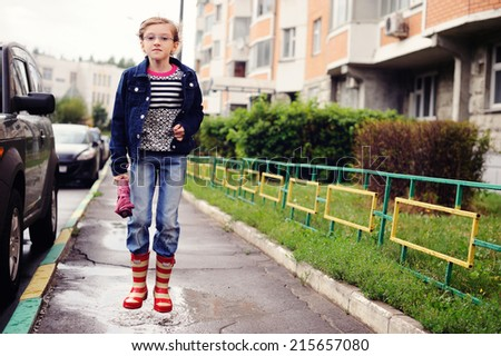 Adorable school age girl in the city street on rainy day - stock photo