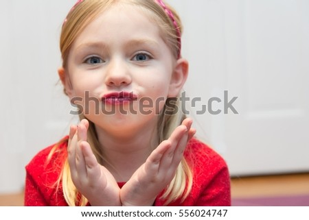 adorable school age girl wearing red and blowing kiss while wearing lipstick