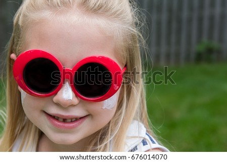 adorable school age girl with sunglasses and bathing suit wearing sunscreen on face to promote sun safety