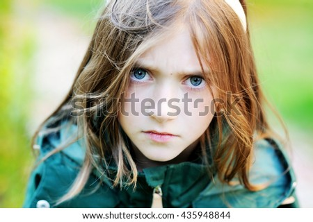 Adorable school aged angry girl portrait outdoor - stock photo