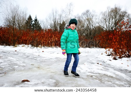 Adorable school aged  girl walking outside in the park in the early spring - stock photo