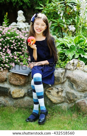 Adorable school aged kid girl in blue uniform dress outdoor with book and apple - stock photo