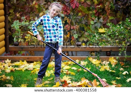 Adorable school aged kid girl in colorful fall clothes picking up autumn leaves in the garden on beauty autumn day - stock photo