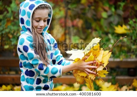 Adorable school aged kid girl in colorful fall clothes picking up autumn leaves in the garden on beauty autumn day