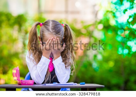 Adorable school girl at desk with notes and pencils outdoor. Back to school. - stock photo