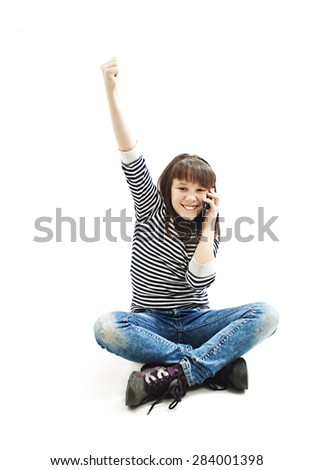Adorable school girl cheering during phone call. Isolated on white background. - stock photo