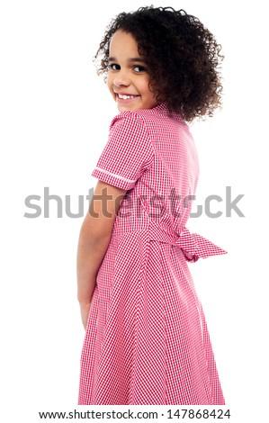 Adorable school girl smiling over her shoulders - stock photo