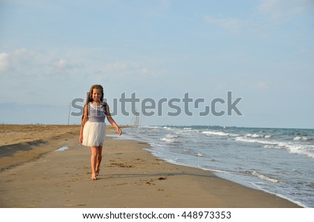 Adorable schoolchild girl with long hair walks on the beach in the evening