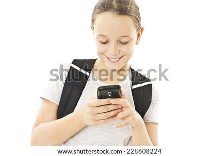 Adorable schoolgirl reading sms on your cell phone. Isolated on white background  - stock photo