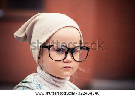 Adorable serious little girl at the street. Big funny glasses on her face. Toned image. Vintage retro style. - stock photo