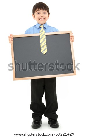 Adorable seven year old boy child in suit holding blank chalkboard over white background. - stock photo