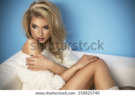 Adorable sexy shapely blond woman in sweater posing on sofa  - stock photo