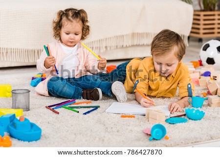 adorable siblings drawing on a floor with colored pencils