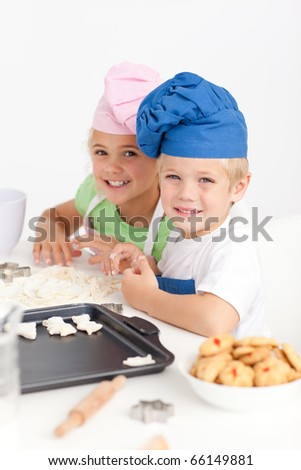 Adorable siblings kneading together a dough in the kitchen to make cookies - stock photo