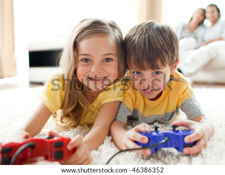 Adorable siblings playing video game in the living room - stock photo