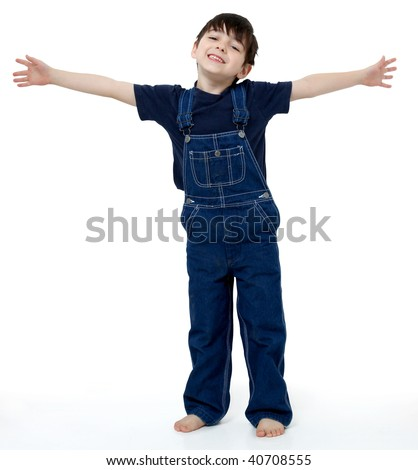 Adorable six year old boy in overalls with his arms stretched out to show size or invite hug.