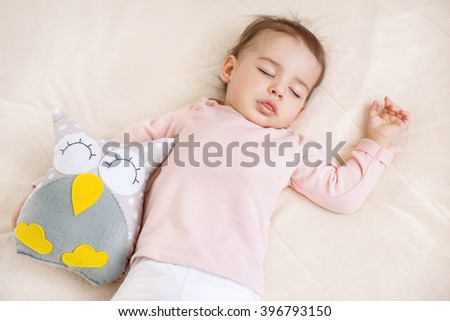 Adorable sleeping baby girl toddler on the bed with an owl toy - stock photo