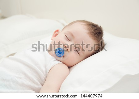 Adorable sleeping baby lying on the pillow with pacifier