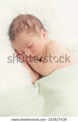 Adorable sleeping newborn baby boy with hands under head. Copy space. Vertical composition.  - stock photo