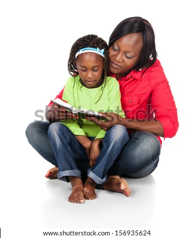 Adorable small african child with braids wearing a bright green shirt and blue jeans and her mother wearing a red shirt. The mom is reading to the girl from a book. - stock photo