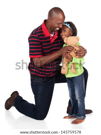Adorable small african child with braids wearing a bright green shirt and blue jeans is playing with her father. He is wearing a red striped shirt and is giving her a teddy bear.