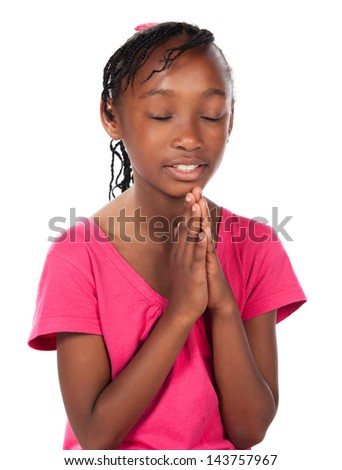 Adorable small african child with braids wearing a bright pink shirt. The girl is kneeling and praying.