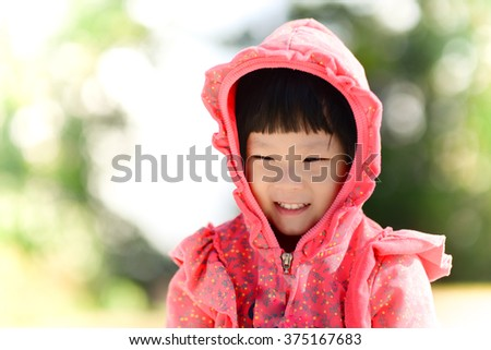Adorable small girl in the hood of red sweater with bokeh background.