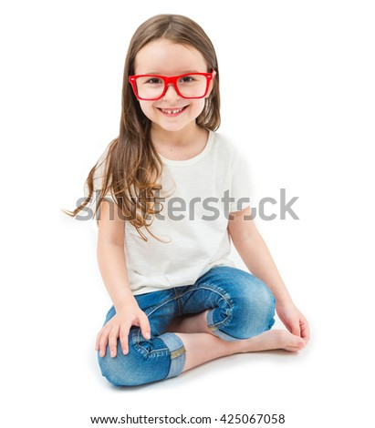 Adorable small girl is sitting down cross-legged in the lotus position barefoot. Red glasse frame white t-shirt and jeans. Long hair lovely kid. Whie background