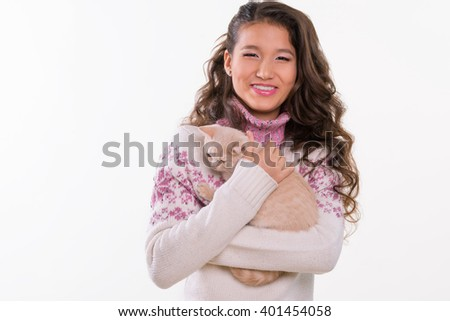 Adorable smile of Asian beauty with ginger kitten on her hands. She hugs lovely animal. Light make-up for a girl. Long curled hair. White background. - stock photo