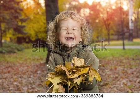 Adorable smiley kid playing with leaves in park - stock photo