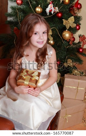 Adorable smiley princess wearing white dress and posing on camera with nice gift box over Christmas tree/Pretty little girl with Christmas gift on Holiday theme