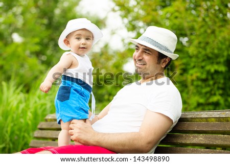 Adorable smiling baby boy with father in the park - stock photo
